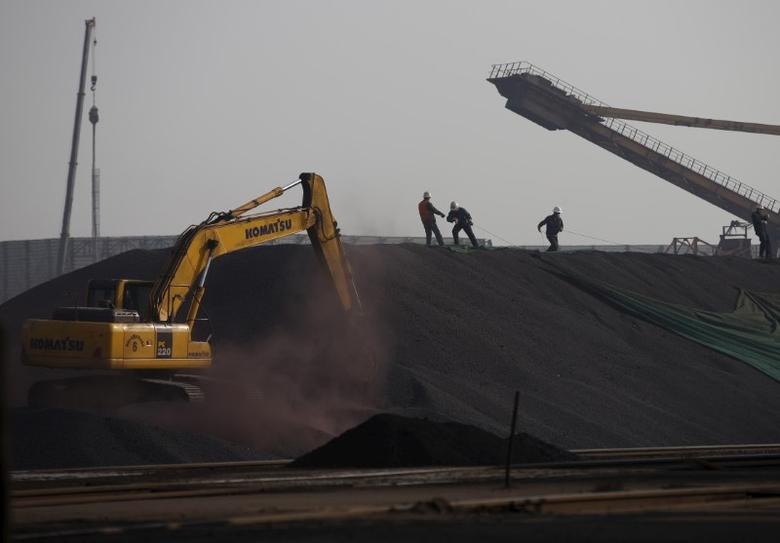 Labors work on a pile of iron ore at a steel factory in Tangshan in China's Hebei Province November 3, 2015. REUTERS/Kim Kyung-Hoon