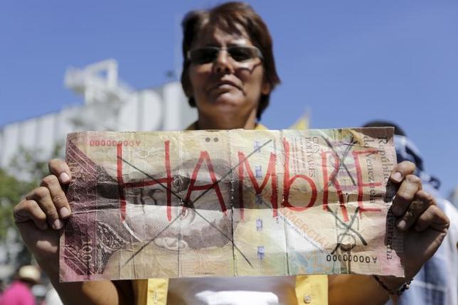 11月28日、ベネズエラ通貨ボリバルの対ドル相場は、非公式の民間市場における取引で過去1カ月間に60%も下落し、1ドル=3500ボリバルに迫る水準となった。写真は、「空腹」と書かれた大きなボリバル紙幣を掲げる野党支持者。首都カラカスで1月撮影(2016年 ロイター/Marco Bello)