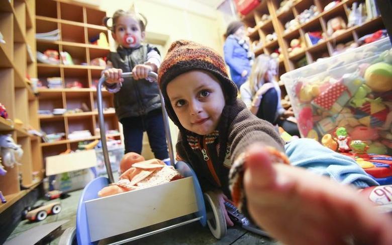Children receive toys at a refugee shelter run by German charity organisation Arbeiter Samariter Bund ASB in Berlin, Germany, December 12, 2015. REUTERS/Hannibal Hanschke