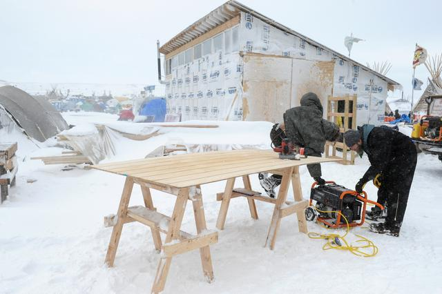 People work on a building project in the Oceti Sakowin camp in a snow storm during a protest against plans to pass the Dakota Access pipeline near the Standing Rock Indian Reservation, near Cannon Ball, North Dakota, U.S. November 29, 2016. REUTERS/Stephanie Keith