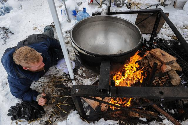 A man makes a fire under a large cooking pot in the Oceti Sakowin camp during a protest against plans to pass the Dakota Access pipeline near the Standing Rock Indian Reservation, near Cannon Ball, North Dakota, U.S. November 29, 2016. REUTERS/Stephanie Keith