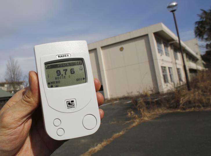A Reuters reporter measures a radiation level of 9.76 microsieverts per hour in front of Kumamachi Elementary School inside the exclusion zone in Okuma, near Tokyo Electric Power Co's (TEPCO) tsunami-crippled Fukushima Daiichi nuclear power plant, Fukushima Prefecture, Japan, February 13, 2016. Survivors exposed themselves to high levels of radiation five years ago while searching for family members swept away by the tsunami that triggered meltdowns at Japan's Fukushima nuclear plant. The disaster in March 2011 killed nearly 16,000 people along Japan's northeastern coast and left more than 2,500 missing. Family members continue to look for the bodies of their missing loved ones, when access to the area is permitted, as they still try to bring closure to their loss. REUTERS/Toru Hanai SEARCH ''THE WIDER IMAGE'' FOR ALL STORIES