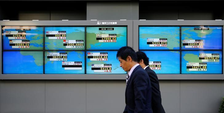 Men walk past an electronic board showing Japan's Nikkei average outside a brokerage in Tokyo, Japan, November 18, 2016.   REUTERS/Toru Hanai