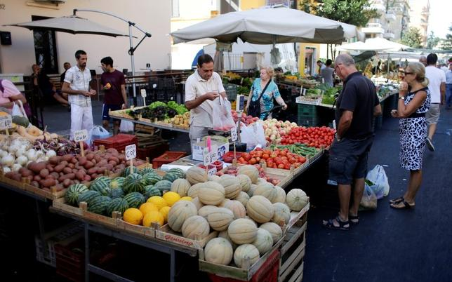 People buy fruit and vegetables in a street market in Rome, Italy, August 11, 2016. Picture taken August 11, 2016. REUTERS/Max Rossi