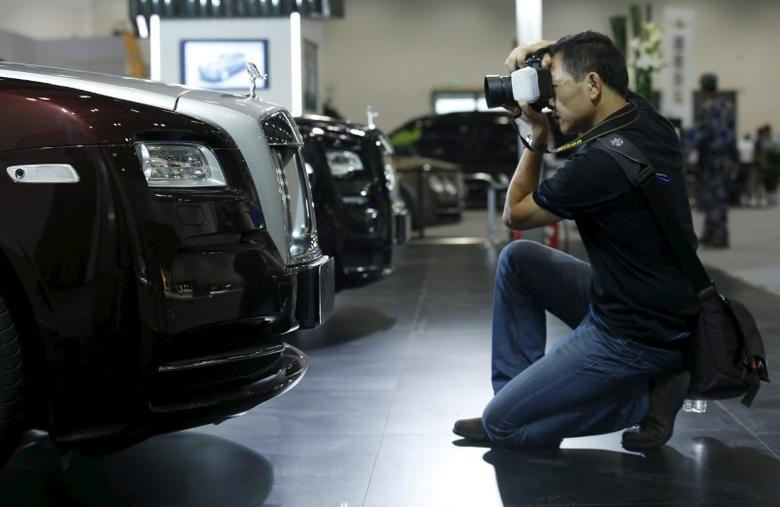 A man takes pictures of a Rolls-Royce Wraith car at the Imported Auto Expo in Beijing, China, September 24, 2015. REUTERS/Kim Kyung-Hoon