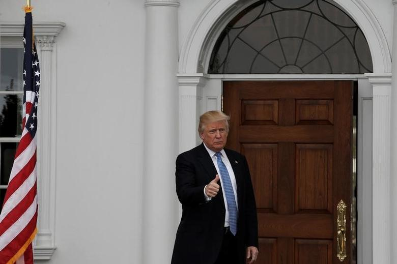 U.S. President-elect Donald Trump gestures from the front door at the main clubhouse at Trump National Golf Club in Bedminster, New Jersey, U.S., November 20, 2016.  REUTERS/Mike Segar