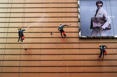 En la imagen, trabajadores limpiando el exterior de un edificio junto a un cartel en Wuxi, provincia de Jiangsu.La expansión del sector de servicios de China se aceleró en noviembre a un ritmo más rápido que en el mes anterior, mostró el jueves un sondeo oficial.REUTERS/Stringer/File Photo