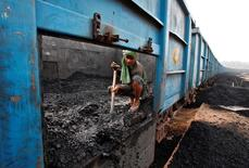 A worker unloads coal from a goods train at a railway yard in Chandigarh, India, July 8, 2014. REUTERS/Ajay Verma/Files
