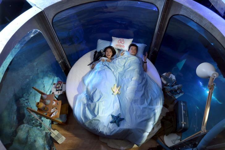 Airbnb contest winners Wu Hao (R) and Tang Di of China pose before spending a night among sharks in an underwater structure installed in the Aquarium of Paris, France April 13, 2016. REUTERS/Charles Platiau/File Photo