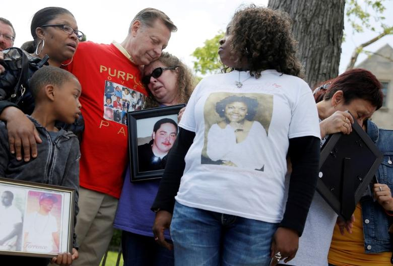 Father Michael Pfleger comforts a woman during a May news conference by a group of mothers who lost children to gun violence, calling for a stop to shootings in Chicago. REUTERS/Jim Young