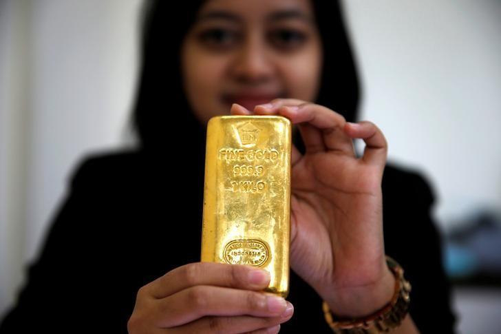 An employee of PT Aneka Tambang Tbk poses with a kilogram of gold bar at PT Antam headquarters in Jakarta, Indonesia, November 28, 2016. REUTERS/Beawiharta