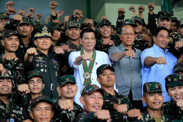 Philippines President Rodrigo Duterte (C) clenches fist with members of the Philippine Army during his visit at the army headquarters in Taguig city, metro Manila, Philippines October 4, 2016. REUTERS/Romeo Ranoco