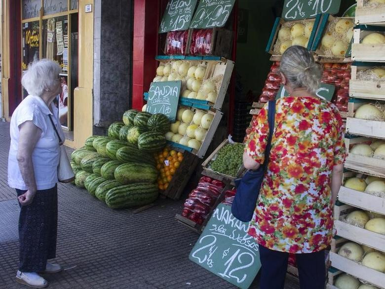 Customers look at the prices in a vegetable store in Buenos Aires January 31, 2014.  REUTERS/Stringer