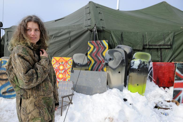 A veteran stands in front of homemade shields in Oceti Sakowin camp as