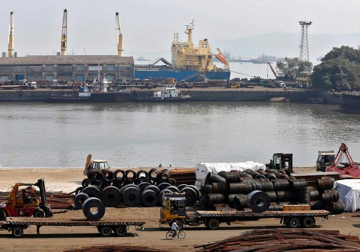 A worker rides his bicycle past steel rims in a dockyard at Mumbai Port Trust in Mumbai November 17, 2014. REUTERS/Shailesh Andrade/File Photo