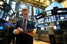 Трейдеры на Уолл-стрит. Индекс Dow достиг рекордного максимума в понедельник, продлив начавшееся после президентских выборов в США ралли благодаря подъему финансовых акций, например, бумаг Goldman Sachs.  REUTERS/Brendan McDermid