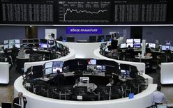 Traders work at their desks in front of the German share price index, DAX board, at the stock exchange in Frankfurt, Germany, December 5, 2016.      REUTERS/Staff/Remote