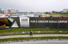 FILE PHOTO --  A man walks past a 1 Malaysia Development Berhad (1MDB) billboard at the funds flagship Tun Razak Exchange development in Kuala Lumpur, March 1, 2015. REUTERS/Olivia Harris/File Photo