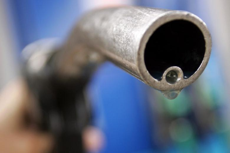 A motorist holds a fuel pump at a Gulf petrol station in London April 18, 2006.  REUTERS/Luke MacGregor/File Photo