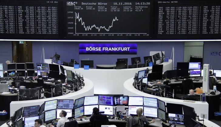 Traders work at their desks in front of the German share price index, DAX board, at the stock exchange in Frankfurt, Germany, November 18, 2016. REUTERS/Staff/Remote