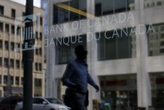 """Человек отражается в стекле, проходя мимо здания Банка Канады в Оттаве. Банк Канады сохранил ключевую ставку в среду, указав на сохраняющуюся неопределенность и """"значительную"""" слабость канадской экономики.   REUTERS/Chris Wattie"""