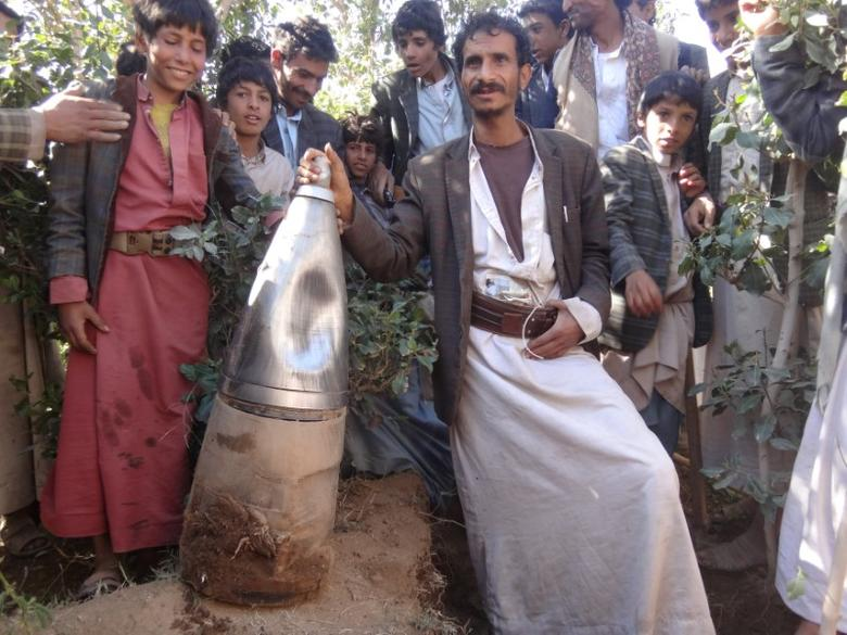 People pose for a picture next to a part of a missile they say was dropped during a Saudi-led air strike near the northwestern city of Saada, Yemen December 7, 2016. REUTERS/Naif Rahma