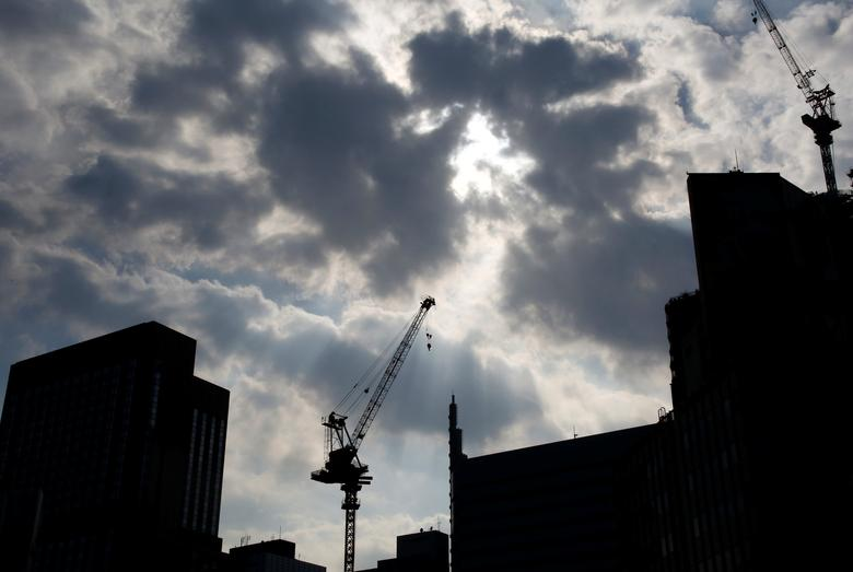 Cranes at a construction site are silhouetted at a commercial area in Tokyo, Japan, August 12, 2016.  Picture taken on August 12, 2016. REUTERS/Kim Kyung-Hoon