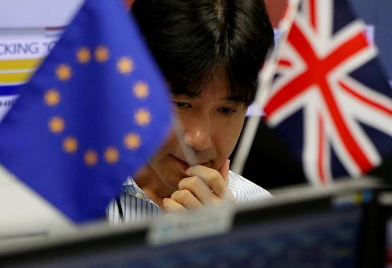 2016年6月24日,东京一家外汇交易公司,图为一名雇员桌面上的英国国旗和欧盟旗帜。REUTERS/Issei Kato
