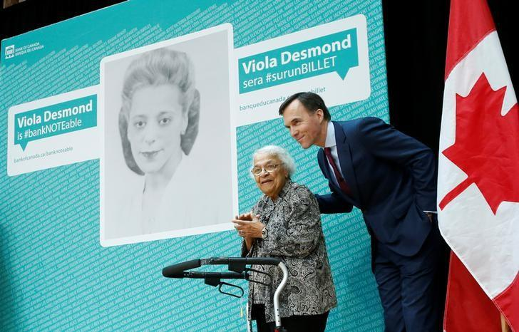 Canada's Finance Minister Bill Morneau stands with Wanda Robson after her sister Viola Desmond was chosen to be featured on a new $10 bank note during a ceremony at the Museum of History in Gatineau, Quebec, Canada, December 8, 2016. REUTERS/Chris Wattie