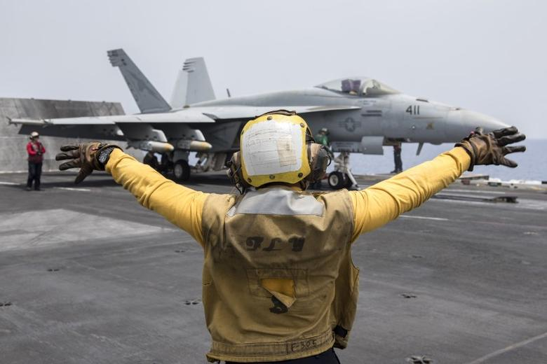 A U.S. Navy crewman directs an F/A-18E Super Hornet fighter jet on the flight deck of the aircraft carrier USS Harry S. Truman in the Mediterranean Sea in a photo released by the US Navy June 3, 2016. U  U.S. Navy/Mass Communication Specialist 3rd Class Anthony Flynn/Handout via REUTERS