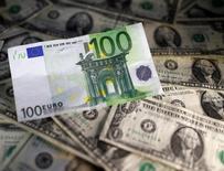 """Доллары и евро. Доллар немного вырос в пятницу на фоне повышения доходности облигаций США, в то время как евро ослаб, поскольку решение ЕЦБ продлить программу скупки активов, хоть и уменьшив её объём с апреля 2017 года, разочаровало валютных """"быков"""".  REUTERS/Dado Ruvic/Illustration"""