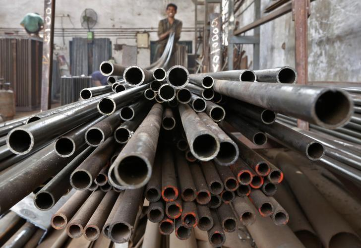 A worker stacks steel pipes in Ahmedabad November 4, 2014. REUTERS/Amit Dave/Files