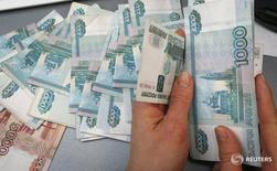 Сотрудник частного магазина в Красноярске пересчитывает деньги. Рубль в пятницу отметился на локальных пиках благодаря оптимистичным ожиданиям в отношении нефтяных цен и реакции рынка на приватизацию Роснефти за валюту, что формально выступает поддержкой рублю; свою роль сыграли нисходящая динамика пары евро/доллар на форексе и закрытие позиций перед выходными днями. REUTERS/Ilya Naymushin