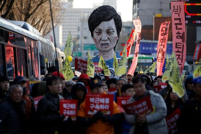 An effigy of South Korean President Park Geun-hye is seen behind people marching towards the Presidential Blue House during a protest calling for South Korean President Park Geun-hye to step down in central Seoul, South Korea, December 10, 2016. The signs read,