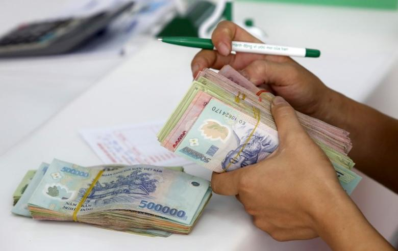 A client counts Vietnamese dong banknotes at a bank in Vinh Yen city, Vietnam, August 19, 2015. Vietnam devalued the dong on Wednesday for the third time this year as authorities moved to bolster a languid export sector facing fresh challenges from a surprise devaluation of the Chinese yuan. REUTERS/Kham