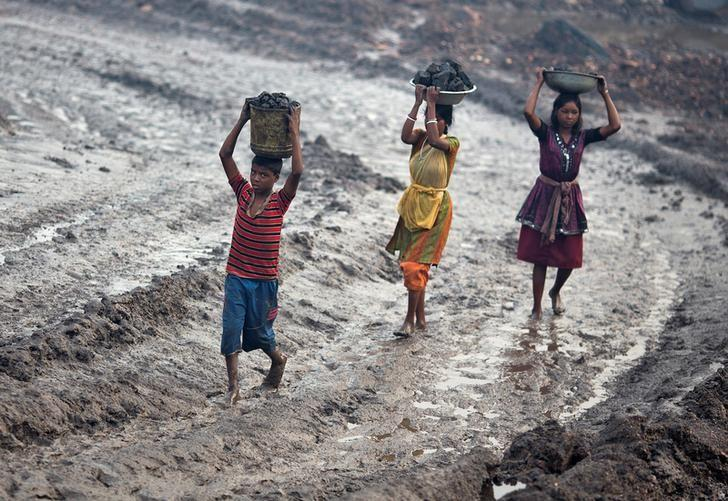 Locals carry coal from an open cast coal field at Dhanbad district, Jharkhand  September 20, 2012. REUTERS/Ahmad Masood/Files