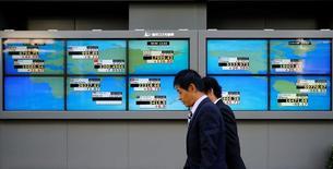 Hombres caminan frente a unas pantallas que muestra el índice Nikkei y otras divisas afuera de una correduría en Tokio, Japón. 6 de julio de 2016.El índice Nikkei de la bolsa de Tokio subió el lunes por quinto día consecutivo, ayudado por un repunte en Wall Street y un yen más débil, y los inversores recogieron acciones defensivas que tuvieron un rendimiento inferior en el avance reciente. REUTERS/Toru Hanai
