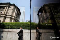 Человек проходит мимо здания Банка Японии в Токио 22 мая 2013 года. Банк Японии может дать более оптимистичную оценку экономике страны в ходе заседания на следующей неделе, сказали источники, поскольку восстановление спроса на развивающихся рынках Азии и признаки оживления частного потребления улучшают перспективы устойчивого восстановления за счёт экспорта. REUTERS/Yuya Shino/File Photo