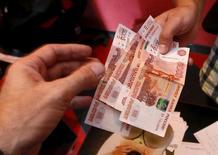 Сотрудник автосервиса принимает деньги от клиента в Красноярске 6 августа 2015 года. REUTERS/Ilya Naymushin