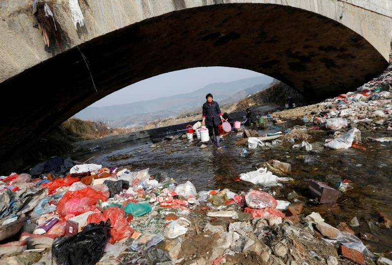 Villagers wash clothes in the garbage-filled Shenling River, in Yuexi county, Anhui province, China February 14, 2015. REUTERS/William Hong/File Photo