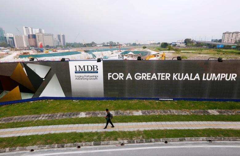 FILE PHOTO --  A man walks past a 1 Malaysia Development Berhad (1MDB) billboard at the funds flagship Tun Razak Exchange development in Kuala Lumpur, March 1, 2015. REUTERS/Olivia Harris/File Photo