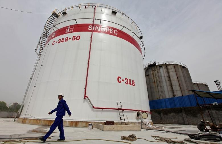An employee walks past oil tanks at a Sinopec refinery in Wuhan, Hubei province, April 25, 2012. REUTERS/Stringer/File Photo
