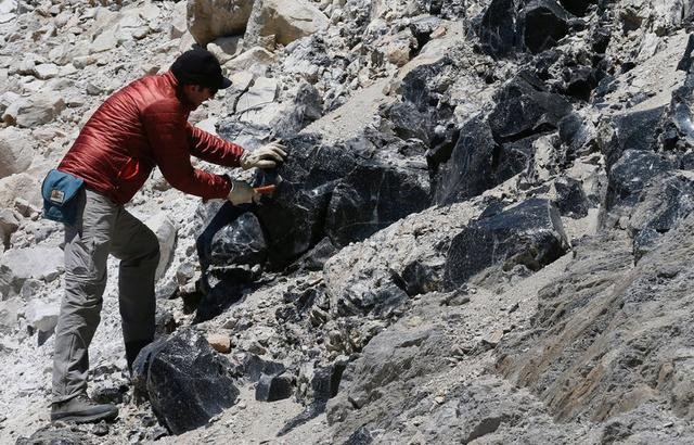 U.S. scientist and geologist of the university of Wisconsin, Brad Singer, breaks rocks to extract mineral samples in the Laguna del Maule (Lagoon of Maule) in the VII region of Talca, south of Santiago,  Chile  November 29, 2016 REUTERS/Rodrigo Garrido