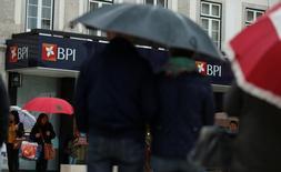 Los accionistas del portugués BPI aprobaron el martes la venta de una participación en el banco angoleño BFA para ceder el control a la empresa de telecomunicaciones angoleña Unitel, un paso para cumplir los requisitos del Banco Central Europeo sobre su arriesgada exposición a la economía de Angola . En la imagen, varias personas pasan junto a una sucursal de BPI en Lisboa,  el 11 de mayo de 2016.  REUTERS/Rafael Marchante