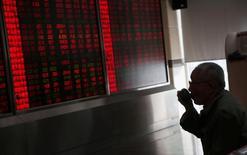 Инвестор смотрит на табло с данными о торгах в брокерской компани Пекина. Китайские фондовые индексы завершили торги среды на месячных минимумах ввиду обещаний регулирующих органов ограничить рискованные инвестиции страховых компаний, подорвав и без того слабый аппетит к риску в преддверии ожидаемого повышения процентных ставок ФРС США. REUTERS/Kim Kyung-Hoon