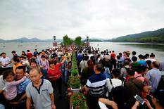 China pretende invertir 2 billones de yuanes (unos 272.000 millones de euros) en el turismo hasta el año 2020 para mejorar la infraestructura  y los servicios públicos, dijo el miércoles la Comisión Nacional de Desarrollo y Reforma (NDRC, por sus siglas en inglés). En esta imagen de archivo, unos visitantes caminan por un puente sobre un lago en Hangzhou, en la provincia de Zhejiang, el 3 de octubre de 2016. REUTERS/Stringer