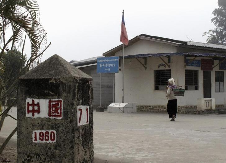 A Myanmar resident walks past a police post at Yinjing village on the other side of the China-Myanmar border close to Ruili, Yunnan province, in this January 12, 2009 file photo. REUTERS/Ben Blanchard/File Photo