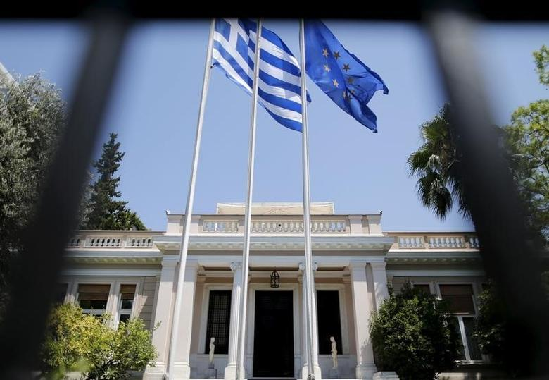 The Greek (L) and the European Union flags flutter in front of Maximos Mansion, the Prime Minister offices, in Athens, Greece, July 13, 2015. REUTERS/Christian Hartmann