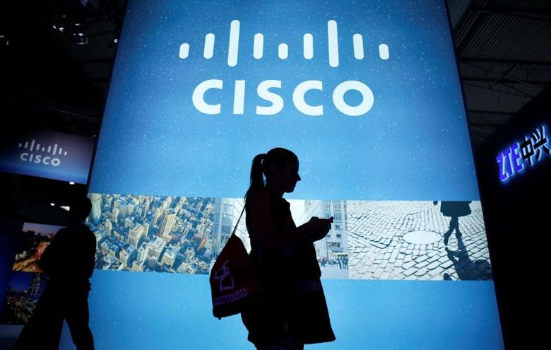 A visitor walks past a Cisco advertising panel as she looks at her mobile phone at the Mobile World Congress in Barcelona February 27, 2014. REUTERS/Albert Gea/File Photo