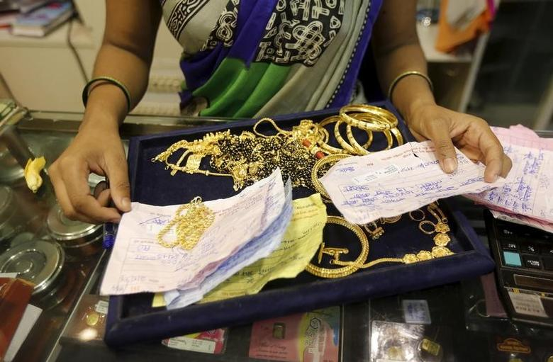 A saleswoman checks the weight and quality of  gold jewellery inside a showroom in Mumbai, India, August 13, 2015.  REUTERS/Shailesh Andrade